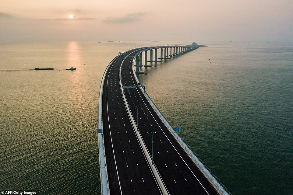 China's president Xi Jinping inaugurates the world's longest sea-crossing bridge that stretches 34 miles and dives INTO THE OCEAN